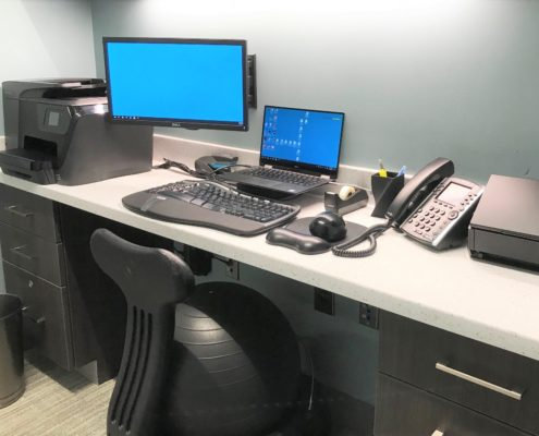 Doctor's desk area with mounted monitor, laptop, and telephone