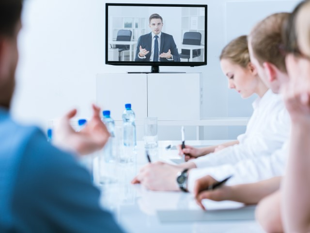 Medical employees in boardroom watching training video