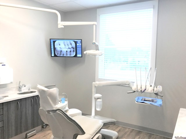 Patient room with dental chair and xray displayed on mounted screen
