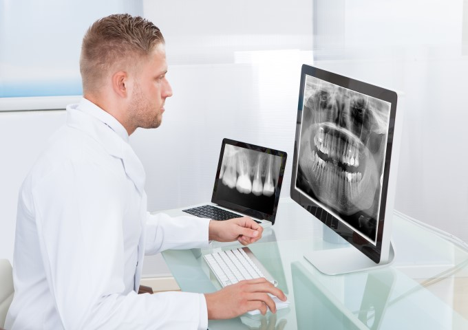 Male dentist looking at xrays across multiple devices via cloud computing services