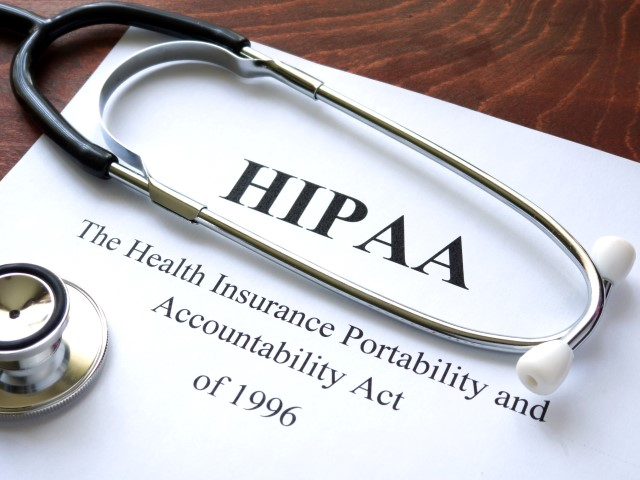 HIPAA compliance paperwork laying on wooden table with stethoscope