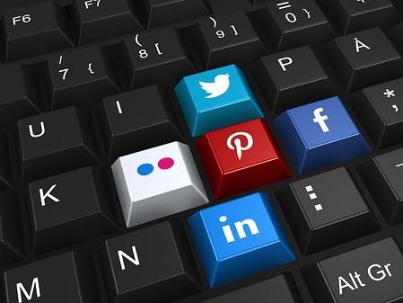 Black keyboard with colored keys for Twitter, Pinterest, Facebook, LinkedIn, and Flickr