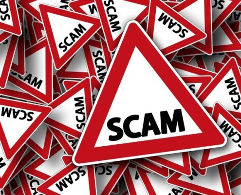 "Red warning signs with text ""SCAM"""