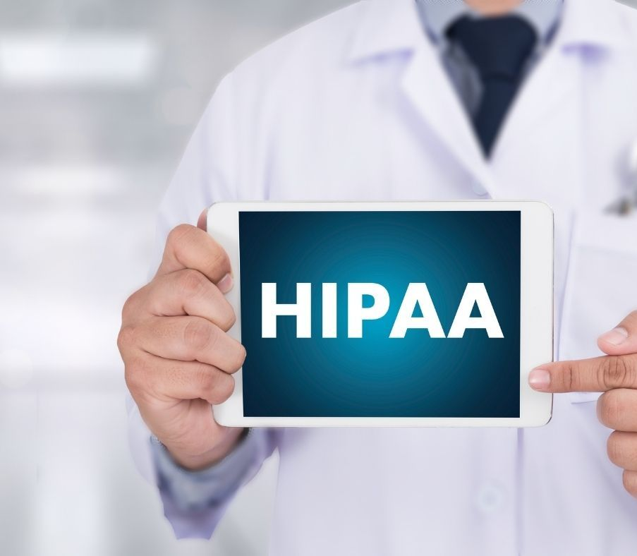 Dentist holding HIPAA Compliance sign